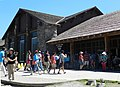 Old Faithful Lodge, visitor walking in front of building (9411306154).jpg