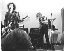A black and white photo, with two band members playing.