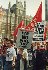 "Protesters marching in front of the Palace of Westminster carrying red banners and placards with anti-poll tax slogans: ""Don't Pay – Don't Collect"""