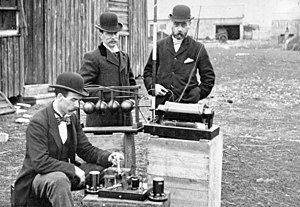 Guglielmo Marconi - British Post Office engineers inspect Marconi's radio equipment during demonstration on Flat Holm Island, 13 May 1897.  The transmitter is at center, the coherer receiver below it, the pole supporting the wire antenna is visible at top.