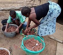 Two teenage girls traditionally prepare shea butter