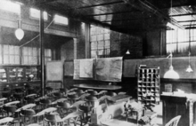 A black and white image of a large room with may chairs in front of a desk and charts. There are bars on the windows.
