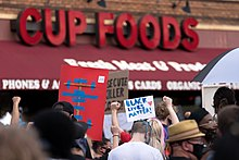 "A brick storefront with the words ""CUP FOODS"" in red. A crowd, some with signs including a ""Black Lives Matter"" sign, stand before it"