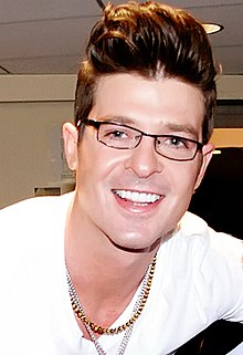 Robin Thicke smiling and wearing glasses.