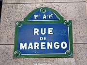 """Blue street sign with green edges. It says in white: """"1er Arrt"""" and below """"RUE DE MARENGO""""."""