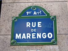 "Blue street sign with green edges. It says in white: ""1er Arrt"" and below ""RUE DE MARENGO""."