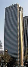 Ground-level view of a brown, rectangular high-rise with rows of black windows; one side is vertically bisected