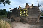 Soldiers in truck reinforced with steel plates.jpg
