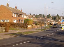 A photograph of a row of post-war housing on a main thoroughfare. The houses are a combination of semi-detached and terraced properties.