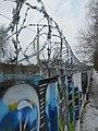 Stacheldraht an Mauer mit Graffiti.jpg
