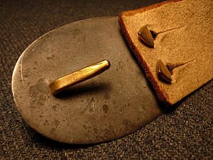 "Belt buckle - Plate-style ""buckle: Back side of original US Civil War buckle, showing bent-arrow chape-end attachment and single-hook mordant"