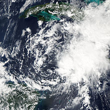 A satellite image of a cluster of storms, weakly circulating about a common center.