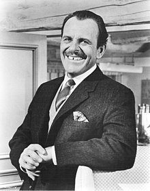 Terry-Thomas from the waist up, in jacket, waistcoat and tie, smiling at the camera