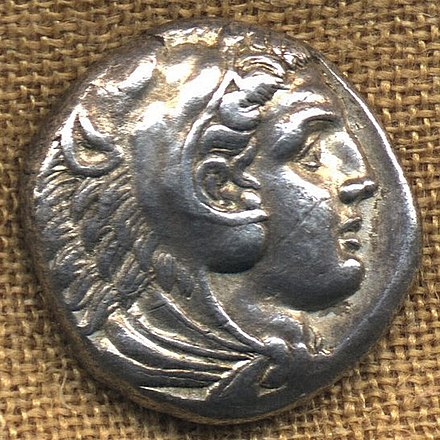 Obverse of the tetradrachm of Alexander the Great, intended to be seen as a deity, wearing the attributes of the hero, Heracles/Hercules. 325 BC. Tetradrachme.wmt.jpg