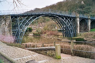 West Midlands (region) - The cast iron Iron Bridge at Coalbrookdale, opened in January 1781 and was the first large-scale object made out of cast iron; but cast iron is not reliably strong due to impurities. Wrought iron, where the carbon is hammered to remove to carbon and impurities is much stronger; the first large-scale wrought iron bridge was the Britannia Bridge over the Menai Strait, only possible due to its innovative box girder design by Robert Stephenson