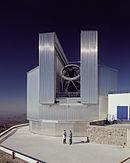 New Technology Telescope: alarge kovový teleskop s dvěma lidmi v přední dává představu o jeho velikosti