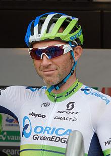 Photo d'un homme portant un casque et des lunettes de soleil, ayant le bras droit levé, devant un panneau publicitaire.
