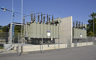 High-voltage transformer fire barriers - High-voltage transformers with bushings on top, separated by a fire barrier