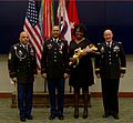 U.S. Army Sgt. 1st Class Phillip Dumas, center, a fires support noncommissioned officer with U.S. Army Central (USARCENT), and his wife, stand with Command Sgt. Maj. John Harris, left, the senior enlisted 131213-A-XY876-003.jpg