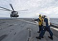 U.S. Navy Boatswain's Mate 1st Class Paul Supnet spots Boatswain's Mate 2nd Class Cost Dumervil as she directs an MH-53E Sea Dragon helicopter as it takes off from the flight deck of the amphibious 131207-N-XJ695-146.jpg