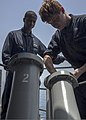 U.S. Navy Chief Cryptologic Technician (Technical) Winston Wright, left, supervises as Cryptologic Technician (Technical) Seaman Apprentice Christopher McCutcheon loads anti-ship missile defense chaff rounds 140629-N-PJ969-061.jpg