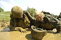 US Navy 040518-N-9693M-009 Midshipmen offer each other encouragement as they maneuver through a mud pit during a rucksack hike as part of Sea Trials.jpg