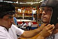US Navy 070119-N-4965F-007 A boxing trainer from USA Boxing Hawaii Association, Inc., adjust the headgear of Electronics Technician 3rd Class Anthony Skillman.jpg