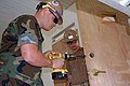 US Navy 090513-F-7522G-002 Builder 2nd Class Jeff Anderson, left, and Construction Electrician 3rd Class Kyle Nixon, assigned to Military Sealift Command hospital ship USNS Comfort (T-AH 20) install a new door.jpg