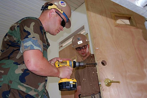 US Navy 090513-F-7522G-002 Builder 2nd Class Jeff Anderson, left, and Construction Electrician 3rd Class Kyle Nixon, assigned to Military Sealift Command hospital ship USNS Comfort (T-AH 20) install a new door