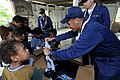 US Navy 090925-N-7478G-354 Storekeeper 1st Class Antonio Hombrebueno, Chief Warrant Officer 3 Carlos Choto, and Chaplain Steven Benefield assigned to the amphibious command ship USS Blue Ridge (LCC 19) hand out clothing to chil.jpg