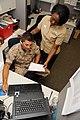 US Navy 110722-N-WJ386-001 Hospital Corpsman 1st Class Ernest Martinez reviews requisitions with Hospital Corpsman 1st Class Cassandra Smythe.jpg