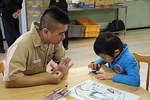 US Navy 111217-N-ZZ999-002 Seaman Recruit Seanangelo Santiago, assigned to the guided-missile cruiser USS Cowpens (CG 63), plays with a child from.jpg