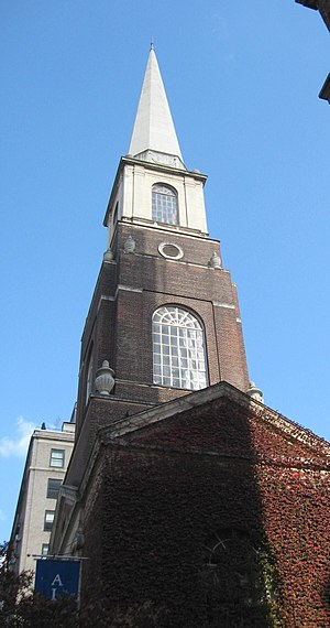 A brick church steeple with pointed wooden upper stage seen from below.