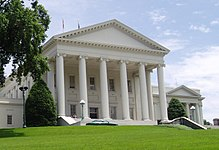 All white Neoclassical building with pediment and six columns rises on a grassy hill with a large American elm tree in the left foreground. Two boxier, but similarly styled wings are attached at the building's rear.