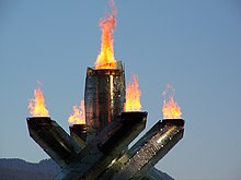 four pillars with flame at their tops surrounding a single fifth pillar in the middle, also with flame at the top. The background is sky with mountain.