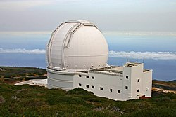 View of large all white building with the biggest part being a spherical shaped section placed atop a rectangular prism. The building sits atop a mountain with clouds showing in the distance above and below the height of the building.