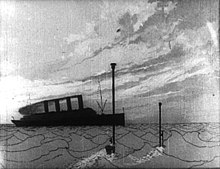 A black-and-white film still. An ocean scene. In the distance is an ocean liner. In the foreground, two periscopes breach the water.