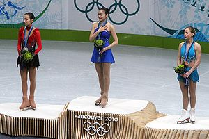Podium - A podium at the 2010 Winter Olympics. The medallists of ladies' single figure skating: Mao Asada (left, silver), Kim Yuna (center, gold), Joannie Rochette (right, bronze).