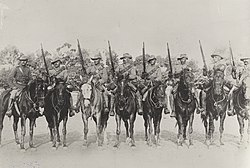 A group of eight soldiers wearing slouch hats with rifles raised into the air on horseback