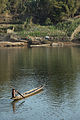 A small boy paddles a boat on the Sekong River.jpg