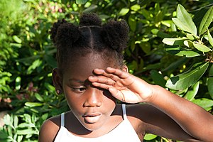 Afro - A little girl wearing a hairstyle of several sections of hair bound with elastics, a style called Afro puffs