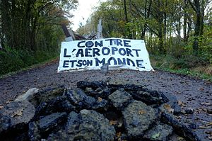 Zone to Defend - A barricade at the Notre-Dame-des-Landes ZAD. Banner reads: AGAINST THE AIRPORT AND ITS WORLD