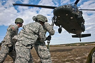 Air Assault Badge - Students at Fort Hood brace against the propwash of a UH-60 Black Hawk as they prepare to attach a slingload during one of the course's practical exercises.