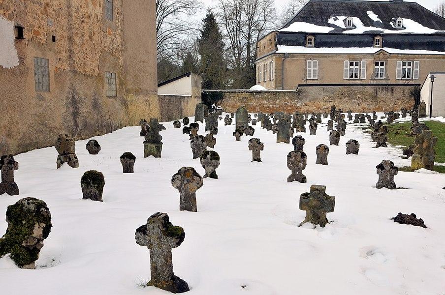 """Um Ale Kierfecht bei der Kierch zu Jonglënster, am Hannergrond d'""""Schlass"""" vum Otto Borrigs."""