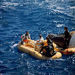 Astronauts Richard Gordon and Pete Conrad sit in life raft while awaiting pickup by a helicopter.jpg