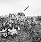 Auxiliary Territorial Service (ATS) girls watch a tug-of-war contest during a sports competition at a mixed 4.5-inch anti-aircraft battery near Edinburgh, 30 July 1943. H31590.jpg