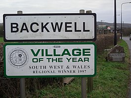 Road signs with Backwell in black writing on white background and below it another sign saying village of the year South West and Wales regional winner 1997.