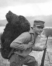 Hunter with a bear's head strapped to his back on the Kodiak ...