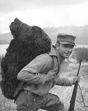 Bear hunting - Hunter with a bear's head strapped to his back on the Kodiak Archipelago