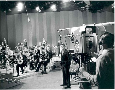 Bernstein with members of the New York Philharmonic rehearsing for a television broadcast Bernstein with TV Camera.jpg